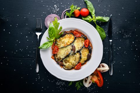 Baked eggplant with parmesan cheese. On a black wooden surface.
