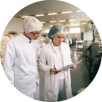 People inspecting food standards in a factory.