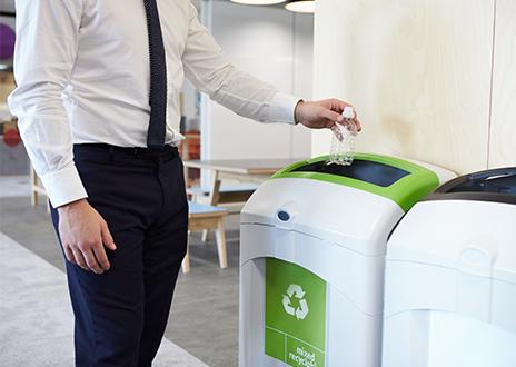 Throwing plastic bottle in recycle bin